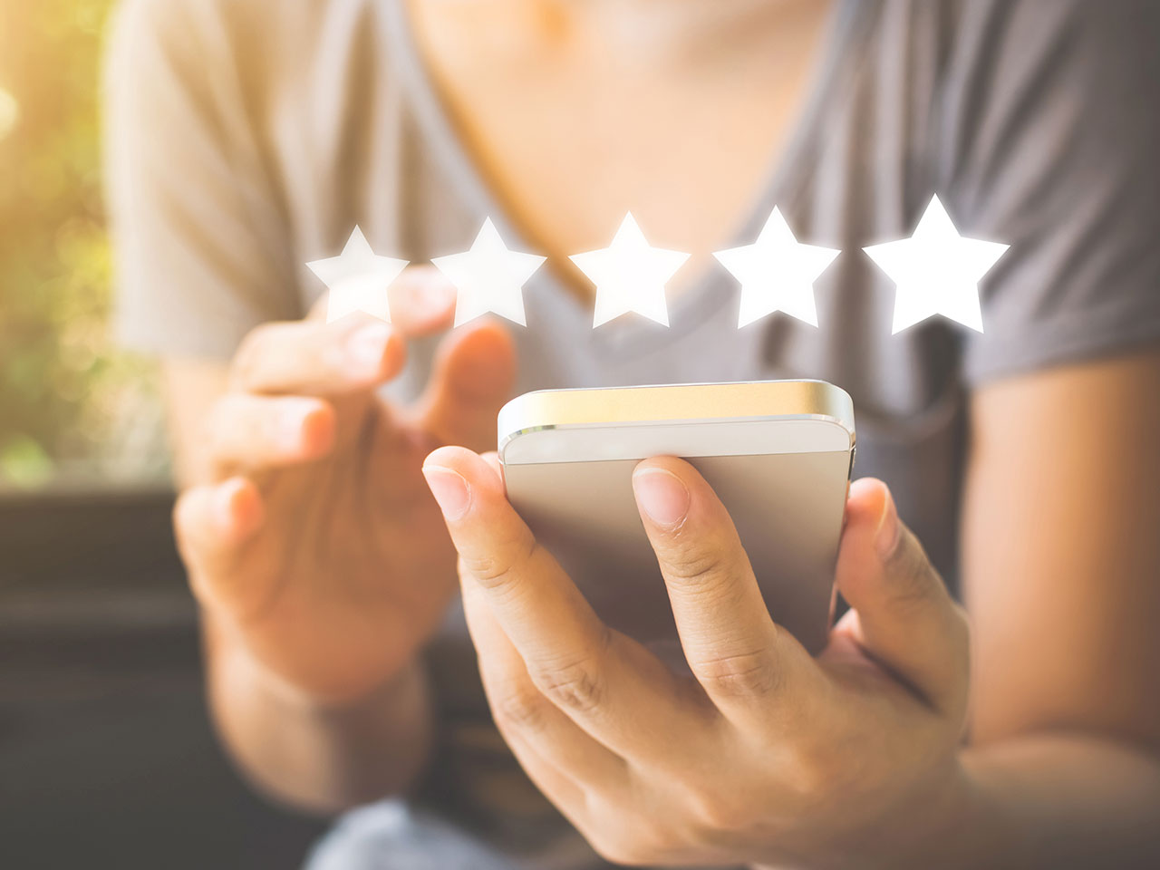 photo of a person holding a smarthphone with 5 stars imposed over the phone, as in Star rating